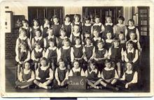 Thelma London at school in Lodin during the second world war. Thelma is holding the placard.