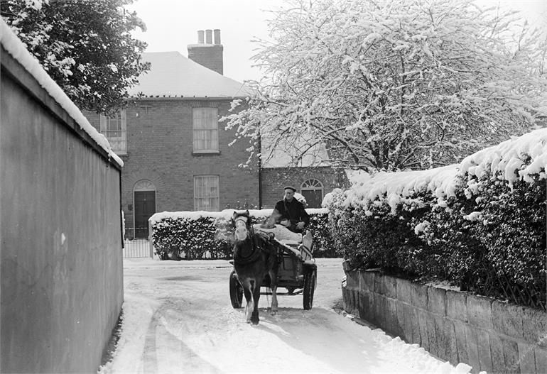 Photograph. Bill Nash on Milk Float on Bank Loke, North Walsham in snow (North Walsham Archive).