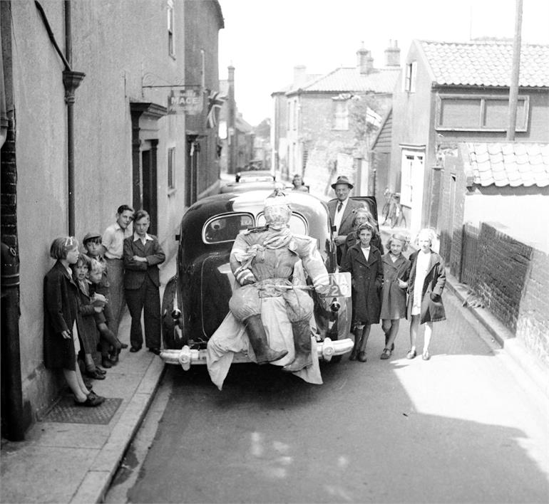 Photograph. Children and figure attached to car on Vicarage Street. (North Walsham Archive).