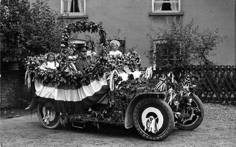Photograph. Decorated car ready for the Coronation Procession, 1911, Palmer's Yard, Vicarage St., North Walsham. Driver has Royal Norfolk Regt. cap badge. (North Walsham Archive).
