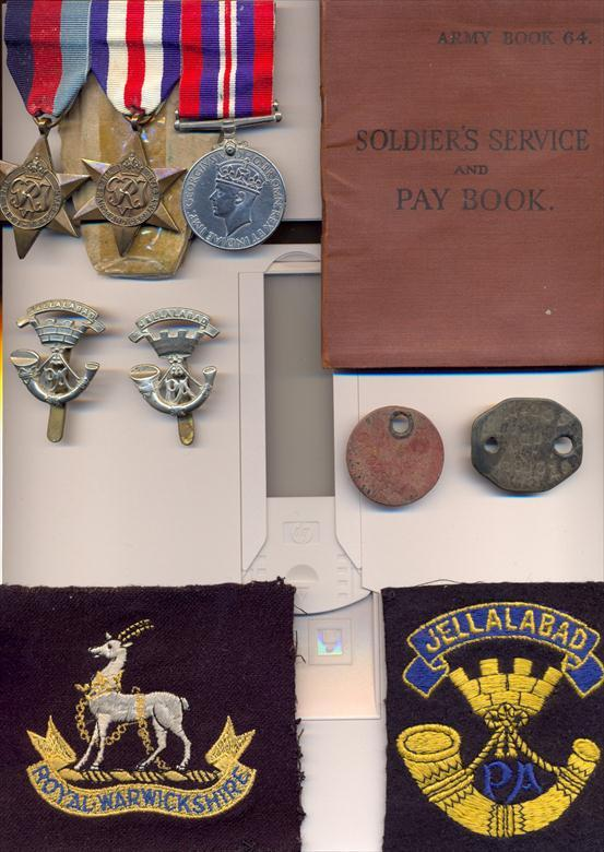 Photograph. Dennis Solly's medal, badges, service books and other things he was issued with during the war. (North Walsham Archive).