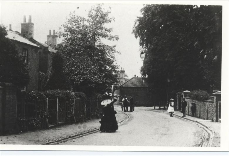 Photograph. Grammar School Road showing two buskers with violin and harp (North Walsham Archive).