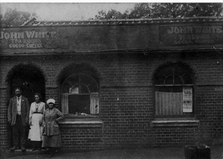 Photograph. John (Joe) White before his Tea Rooms, with family, in Kings Arms Street, North Walsham. (North Walsham Archive).
