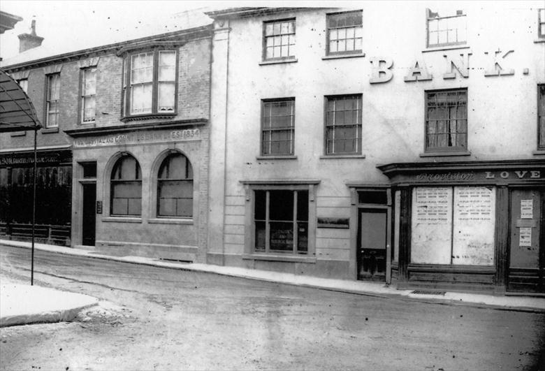 Photograph. Market Place end of Kings Arms Street. Cubitt's Grocers on left; Capital & Counties Bank; London & Provincial Bank; Loveless, flavouring essences. (North Walsham Archive).