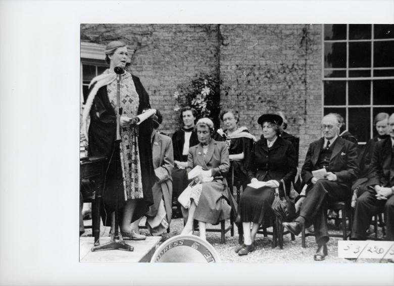 Photograph. Miss M S Middlewood, Head North Walsham Girls' High School 1947...1967, conducts Prize Giving outside before the new hall was built. (North Walsham Archive).