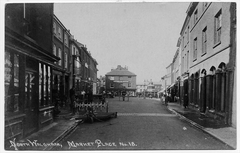 Photograph. North Walsham Market Place, looking west. Note brick pathway to cross the muddy road. (North Walsham Archive).