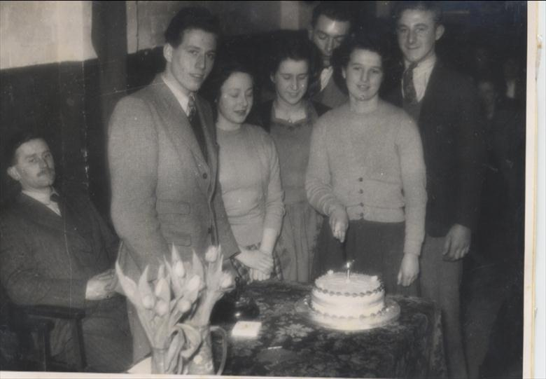 Photograph. North Walsham Youth Club, first anniversary cake cut by Edith Cutting, 1949. (North Walsham Archive).
