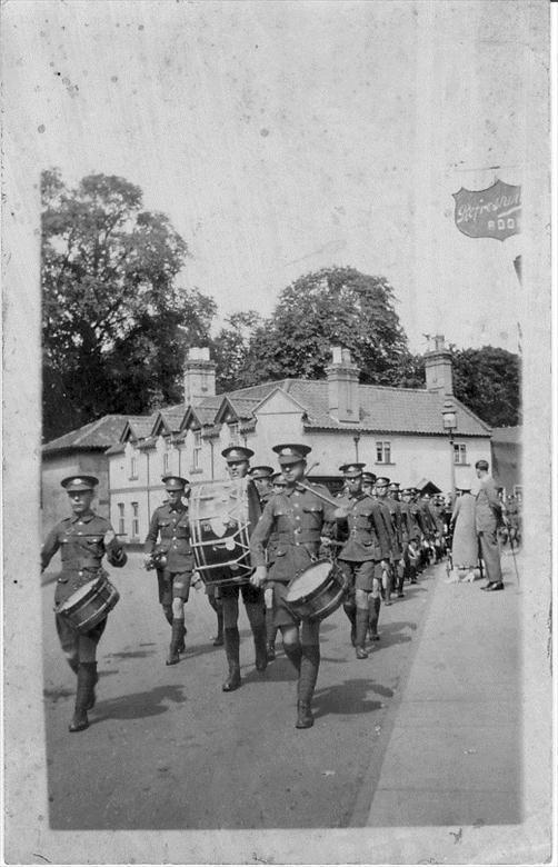 Photograph. Paston School Cadet Force, led by its band, marching along Norwich Road. Bull Inn in the background. (North Walsham Archive).