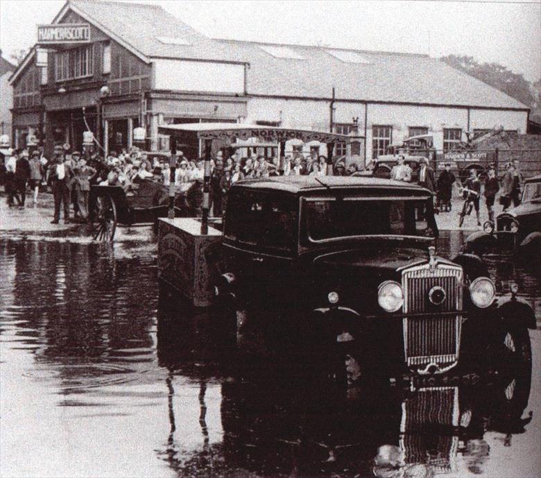 Photograph. Peruzzis' ice cream cart being towed through floods under the M&GN Railway Bridge. Harmer & Scott's Garage in background (North Walsham Archive).