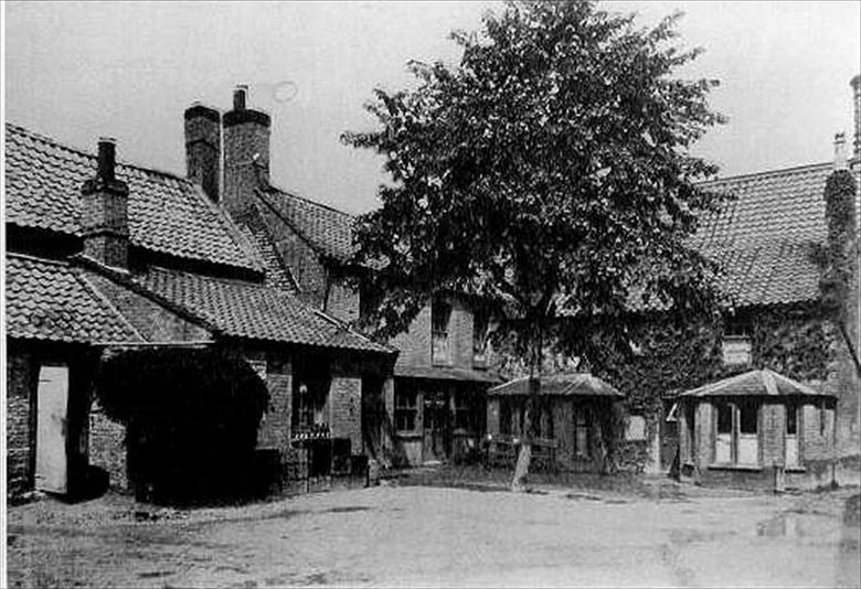 Photograph. Rear view of the Cross Keys Hotel taken from the Cross Keys Yard. The door to the Lounge Bar is on the far left. (North Walsham Archive).