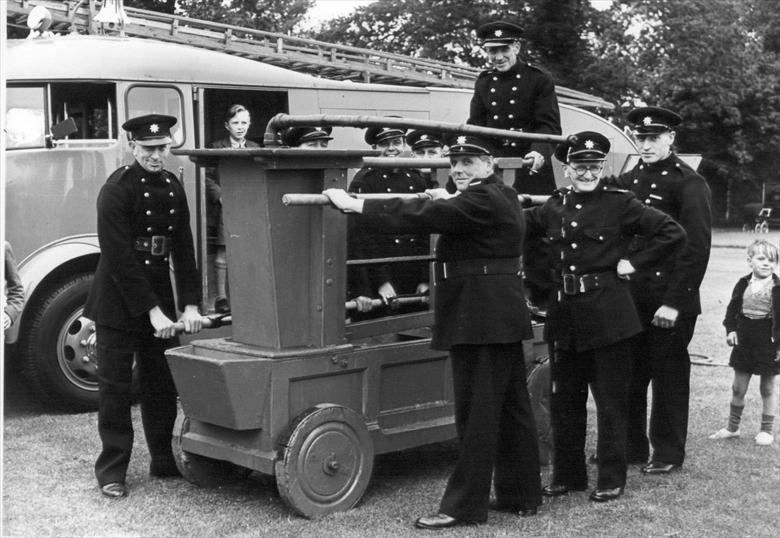 Photograph. The rebuilt North Walsham fire pump exhibited after its restoration by the Fire Service (North Walsham Archive).