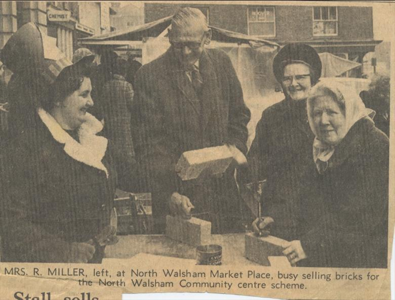 Photograph. Selling bricks at 2s..6d each to raise money for a Community Centre in North Walsham. (North Walsham Archive).